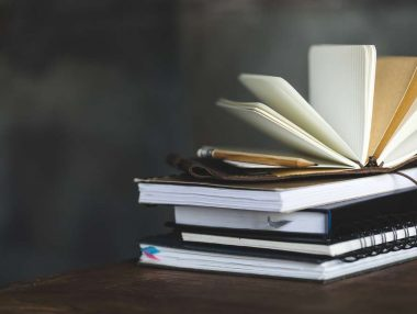 stack of books and diaries on dark grey with copy space