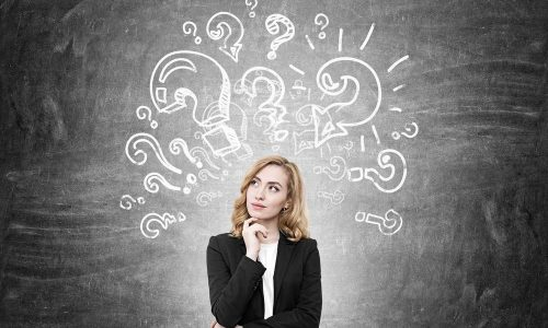 Woman in suit standing near blackboard with question marks on it. Concept of challenging problem solving. Hand on chin