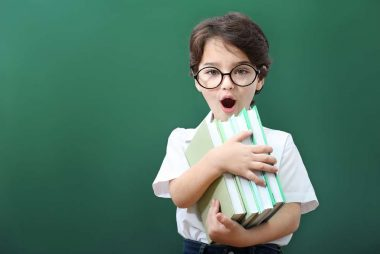 Cute little boy in glasses with books on green background
