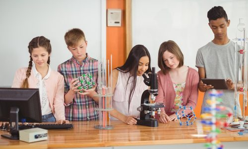 Group of students experimenting molecule model in laboratory at school