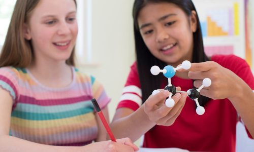 Two Female Pupils Using Molecular Model Kit In Science Lesson
