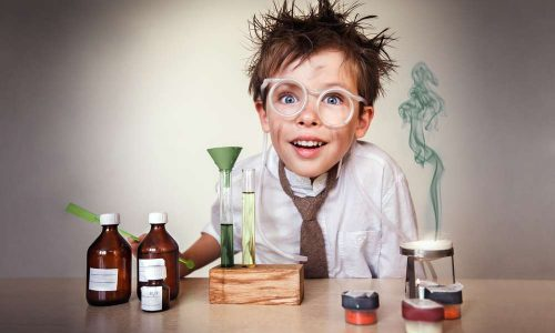 Crazy scientist. Young boy performing experiments