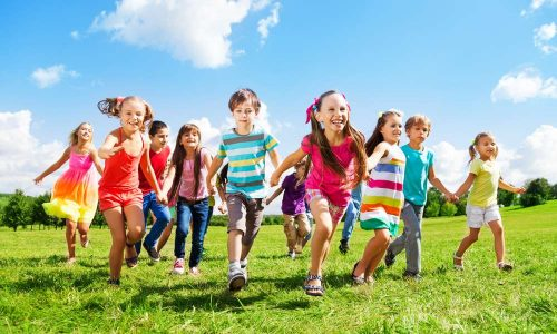 Many different kids, boys and girls running in the park on sunny summer day in casual clothes