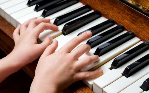 Llittle girl trying to play the piano with her little fingers.
