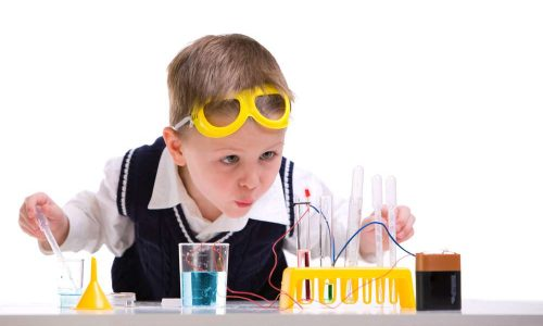 Crazy scientist. Young boy performing experiments with battery and small lamp.