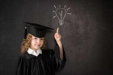 Smart kid in class. Happy child against blackboard. Idea concept