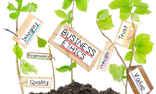 Photo of plants growing from soil heaps with BUSINES ETHICS conceptual words written on paper cards